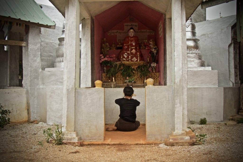 Woman prays before Buddha, Say Kinn, Burma