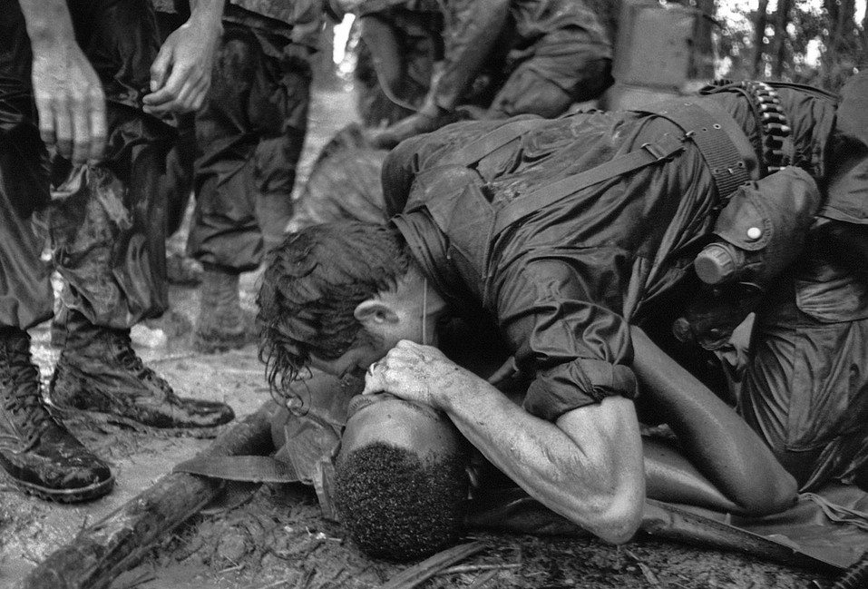Image [A medic of the 101st Airborne Division attempts to save the life of a fellow medic wounded during the assault against the North Vietnamese at Hamburger Hill. May 19, 1969. The wounded medic later died.][Photo: Hugh Van Es / AP]