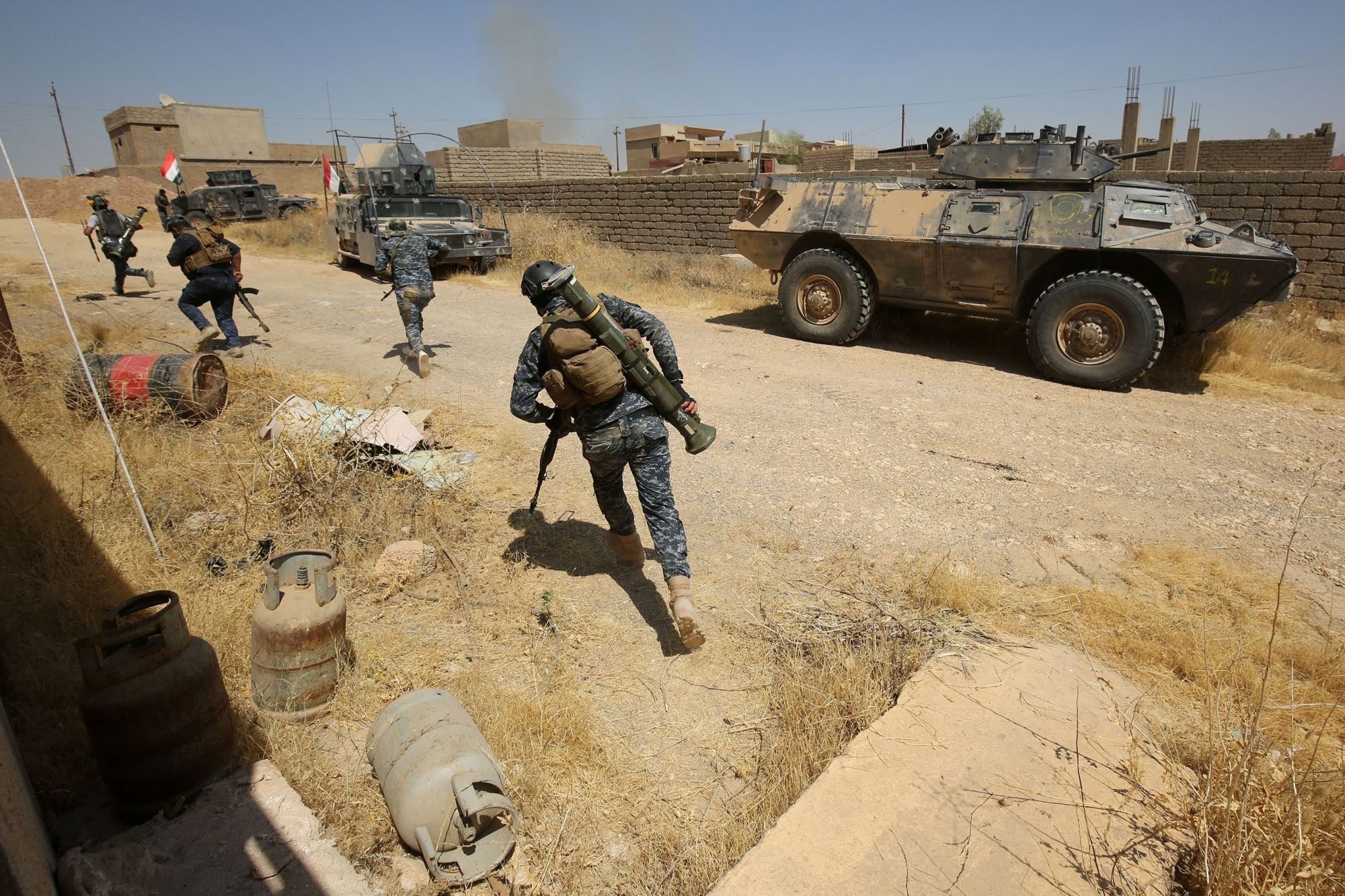 Image Iraqi forces, backed by the Hashed al-Shaabi (Popular Mobilisation units), advance through Tal Afar's al-Wahda district during an operation to retake the city from the Islamic State (IS) group on August 24, 2017. (AFP PHOTO / AHMAD AL-RUBAYE)
