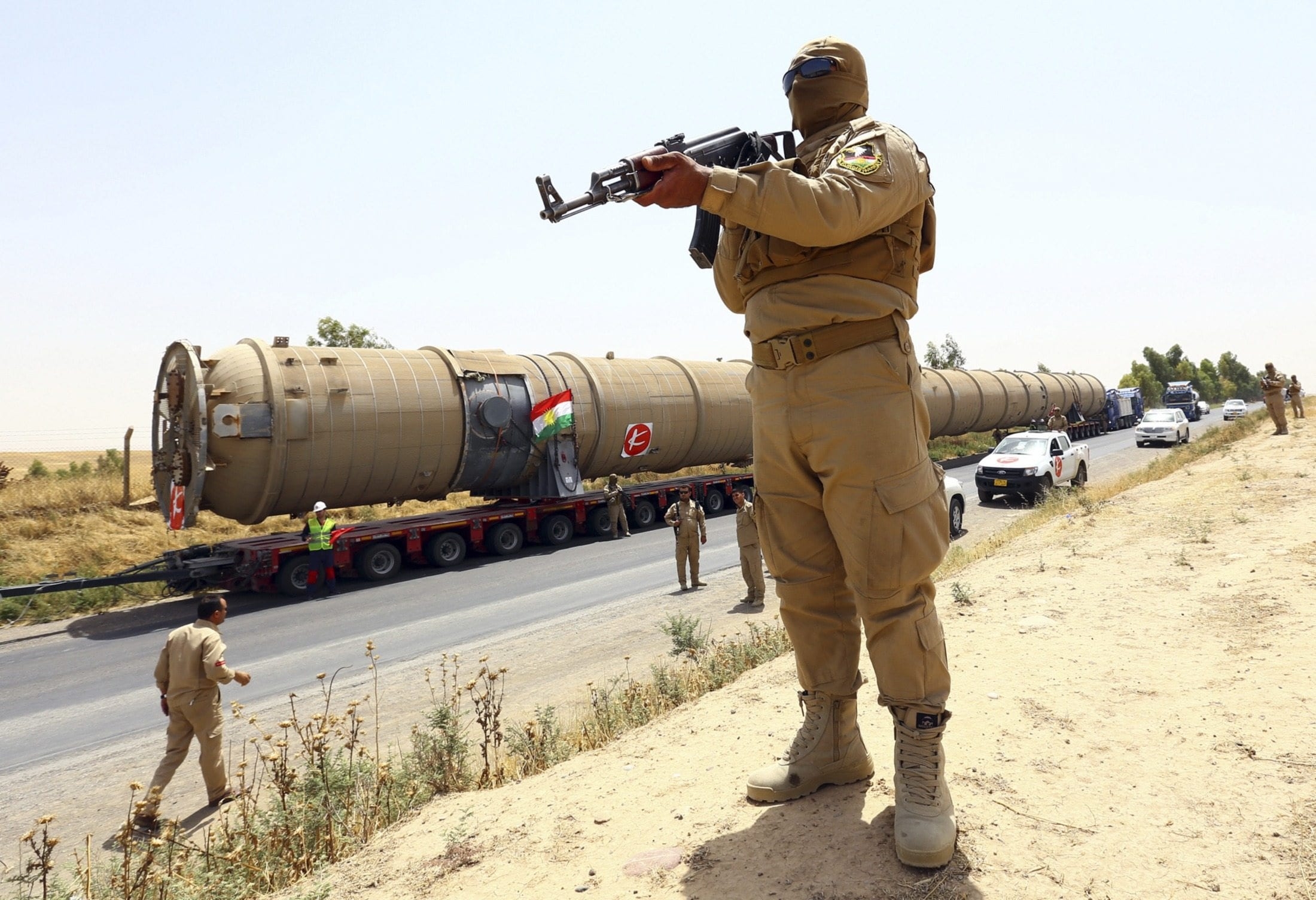 Image A member of the Kurdish security forces takes up position with his weapon as he guards a section of an oil refinery, which is being brought on a truck to Kalak refinery in the outskirts of Arbil, in Iraq's Kurdistan region, July 14, 2014. (REUTERS/Stringer)