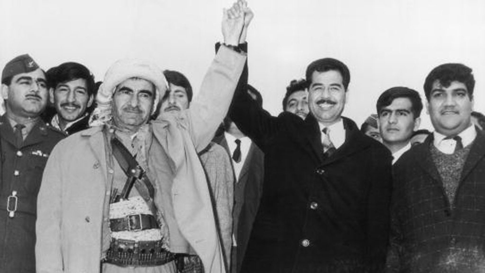 Image Mulla Mustafa Barzani, leader of the Kurdistan Democratic Party, holds hands with Saddam Hussein (BBC)