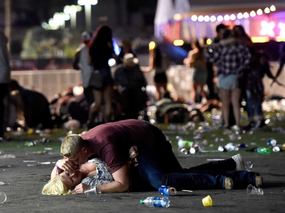 Image A man lays on top of a woman as others flee Las Vegas shooting (ABC News