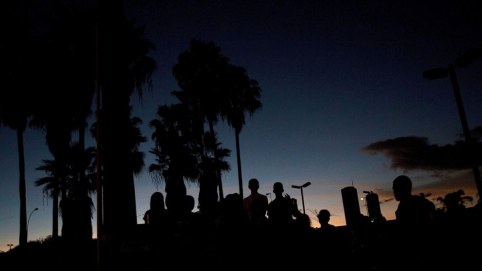 Image A group sings Christmas carols at a dark Venezuela Square in Caracas, Venezuela, Dec. 22, 2017 (AP Photo/Fernando Llano)