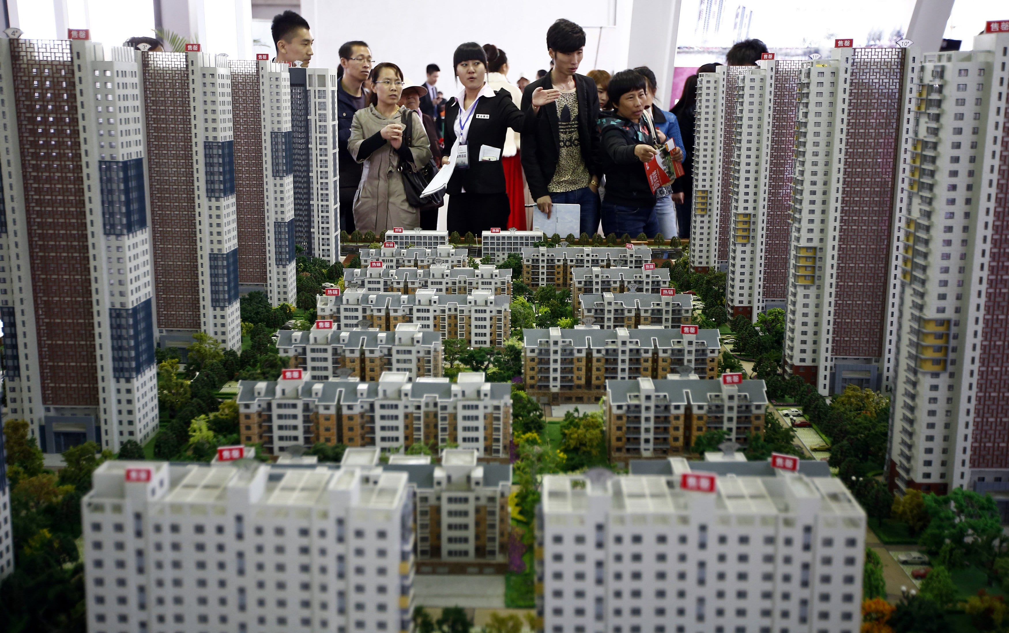 Image A sales assistant talks to visitors in front of models of apartments at a real estate exhibition in Shenyang, Liaoning province April 17, 2014. [Sheng Li—Reuters]