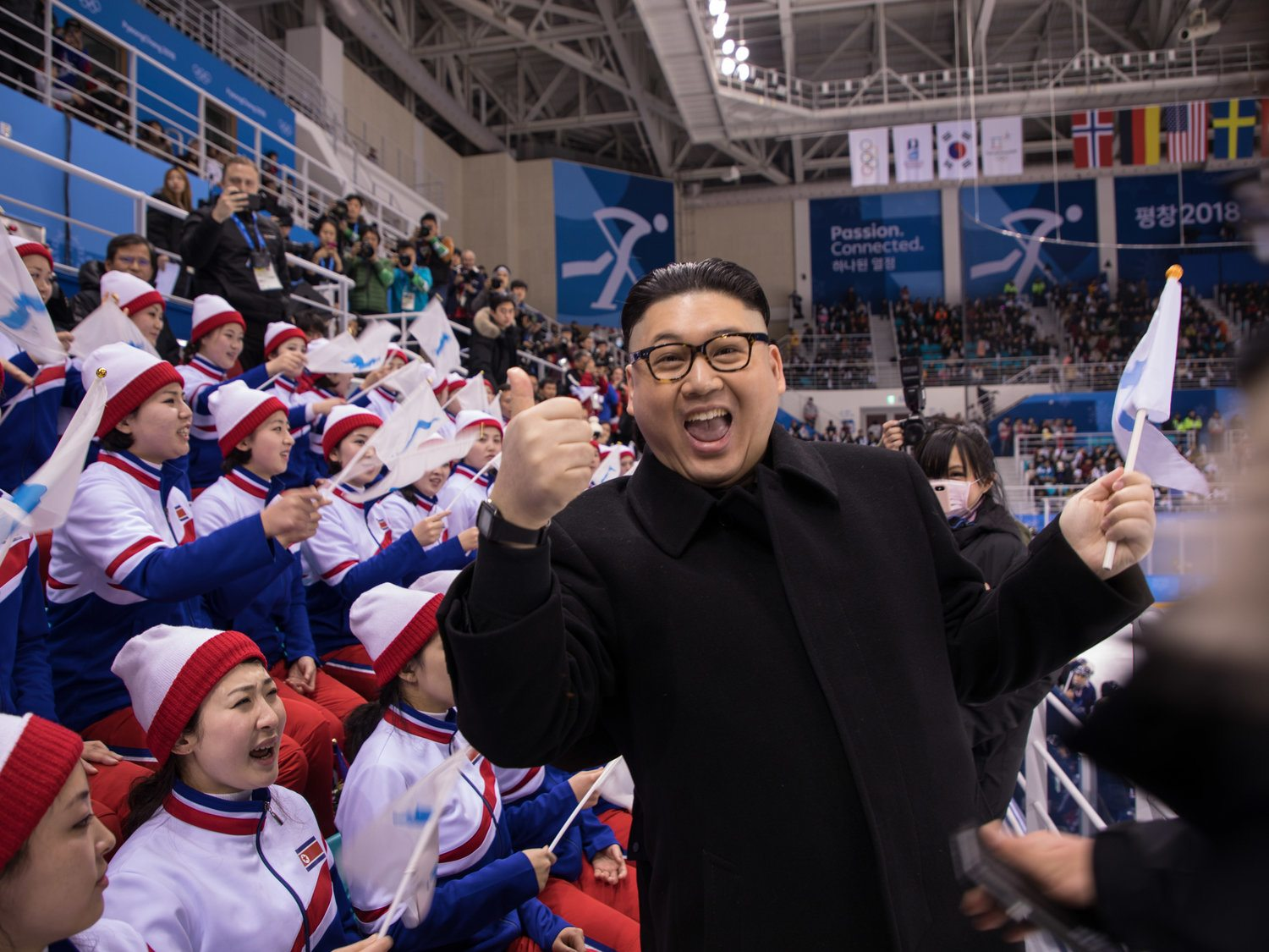 "Image A man impersonating Kim Jong Un in front of the North Korean cheerleaders at an Olympic women's ice hockey game at the South Korean Olympics. The blurred hands on the side of the image are North Korean ""minders"" moving in to whisk him away. (Yelim Lee/AFP)"
