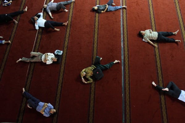Image Indonesian Muslim men sleep as they wait for the time to break their fast at Istiqlal Mosque in Jakarta, Indonesia, on July 23. (Tatan Syuflana/Associated Press)