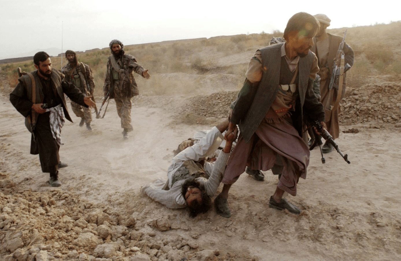 Image Northern Alliance soldiers dragging a captured ISIS fighter during their advance on Kabul in 2001. (James Hill)