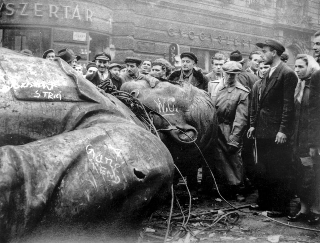 Image [Oct. 24, 1956, people gather around a fallen statue of Soviet leader Josef Stalin in front of the National Theater in Budapest, Hungary. The uprising in Hungary began on Oct. 23, 1956 with demonstrations against the Stalinist regime in Budapest and was crushed eleven days later by Soviet tanks amid bitter fighting. (AP Photo / Arpad Hazafi)
