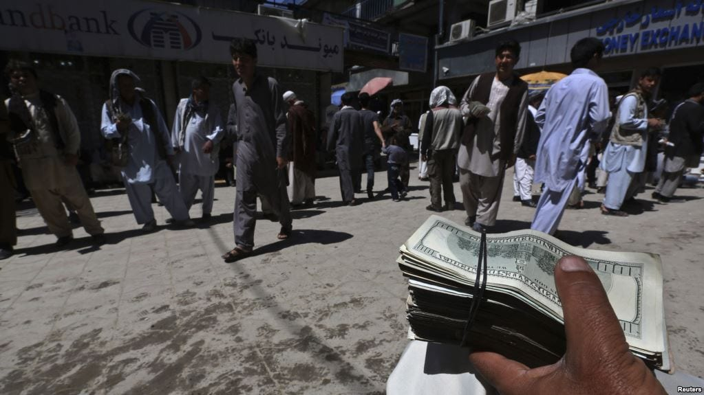 Image A money changer holds a stack of U.S. dollars at Kabul's largest money market April 23, 2014. (Reuters)]
