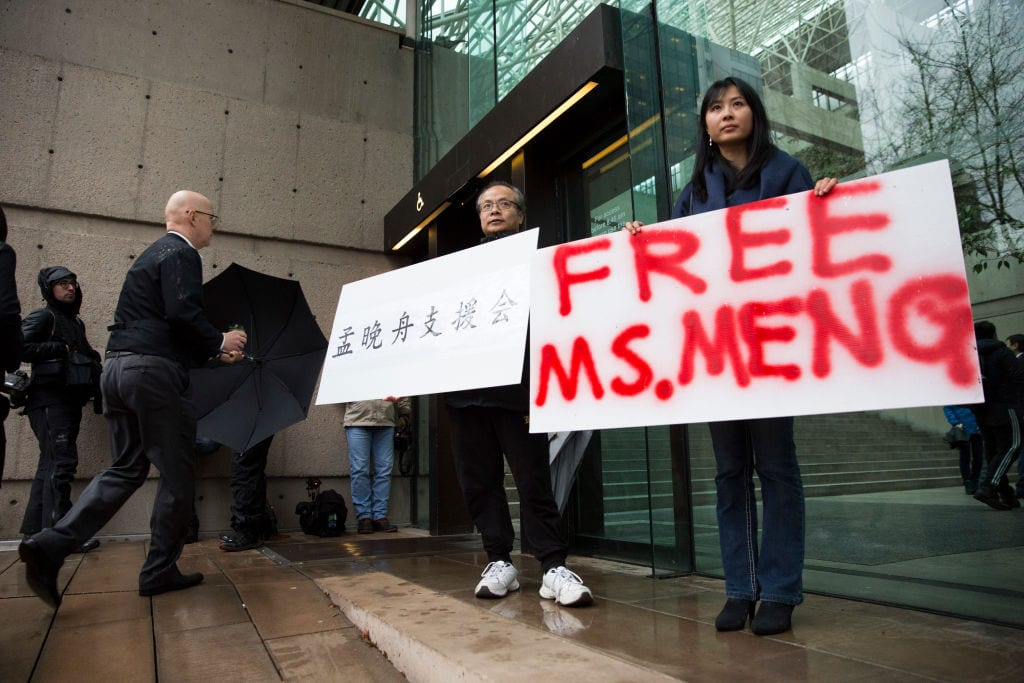 Image Robert Long (L) and Ada Yu hold signs in favor of Huawei Technologies Chief Financial Officer Meng Wanzhou outside her bail hearing at British Columbia Superior Courts following her December 1 arrest in Canada for extradition to the US, December 11, 2018. (Photo by Jason Redmond / AFP)