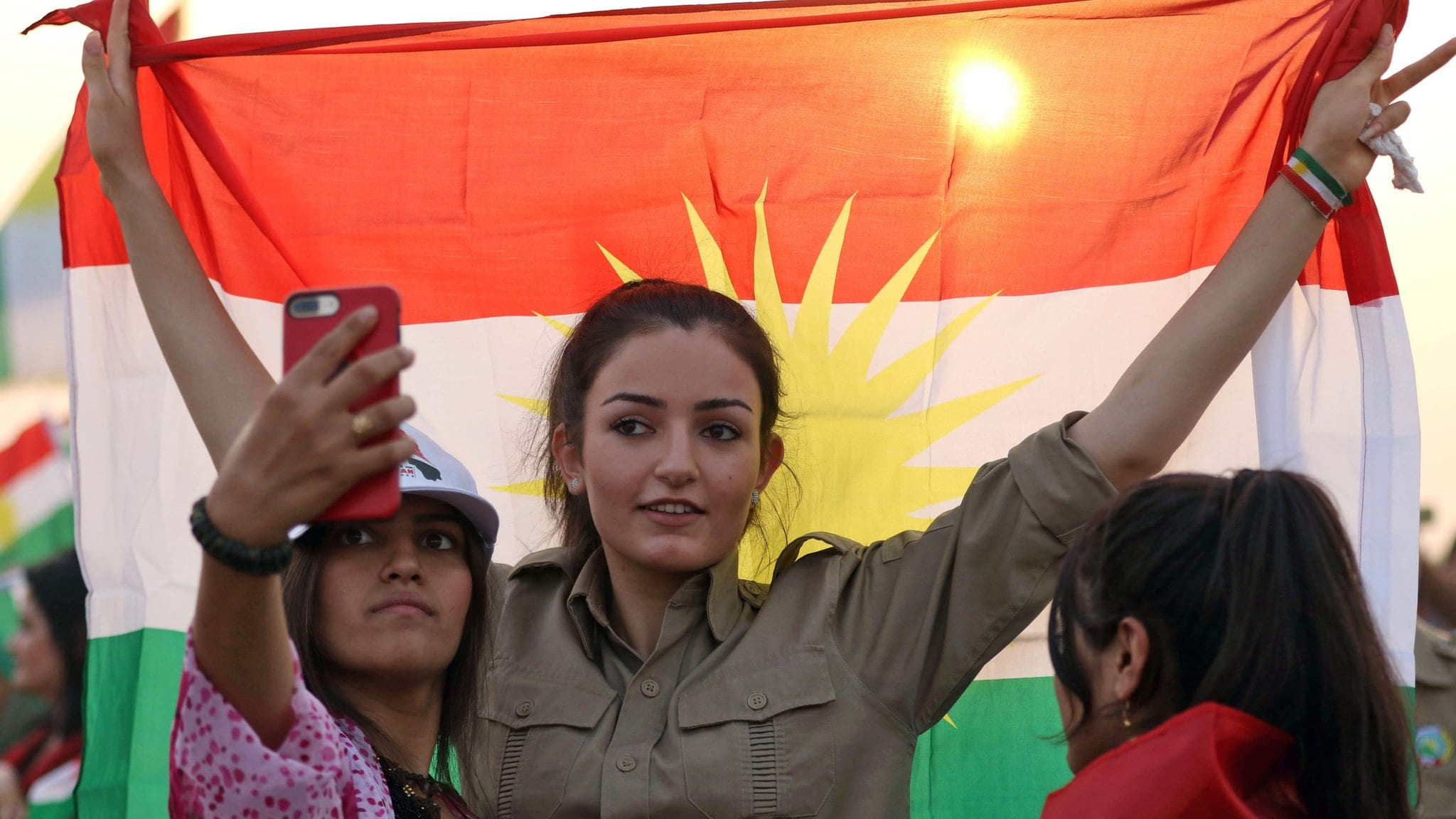 Image [An Iranian Kurdish woman holds a Kurdish flag as she takes part in a gathering before the Iraqi Kurdistan independence referendum, which was held on September 25, 2017. (AFP)]