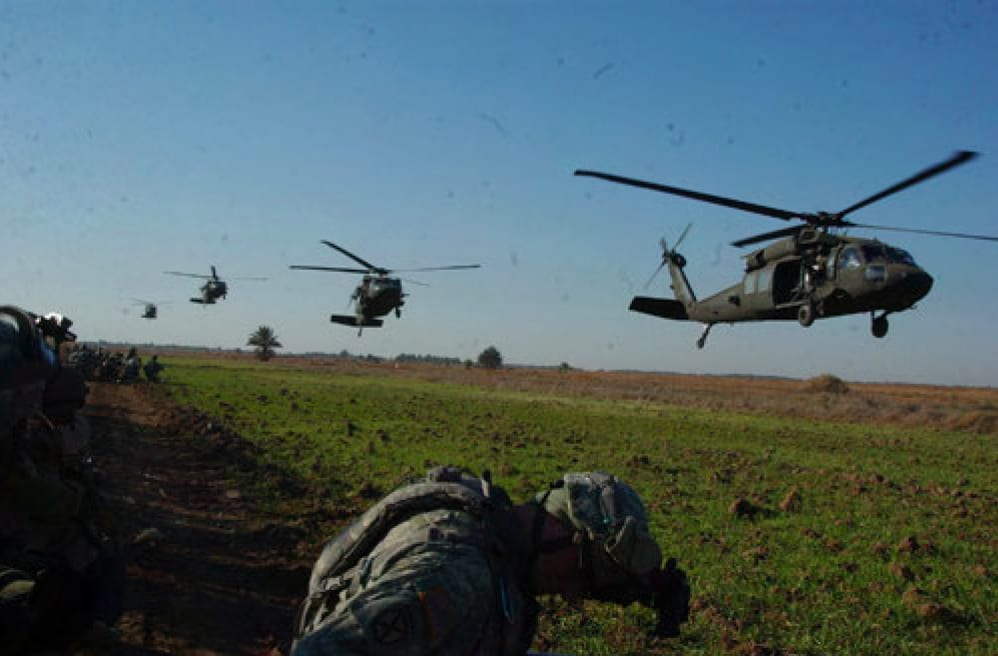 Image [American and Iraqi Soldiers wait as U.S. Army UH-60 Black Hawk helicopters approach their landing zone near Mahmudiyah][Source: DoD photo by United States Forces Iraq (Released)]