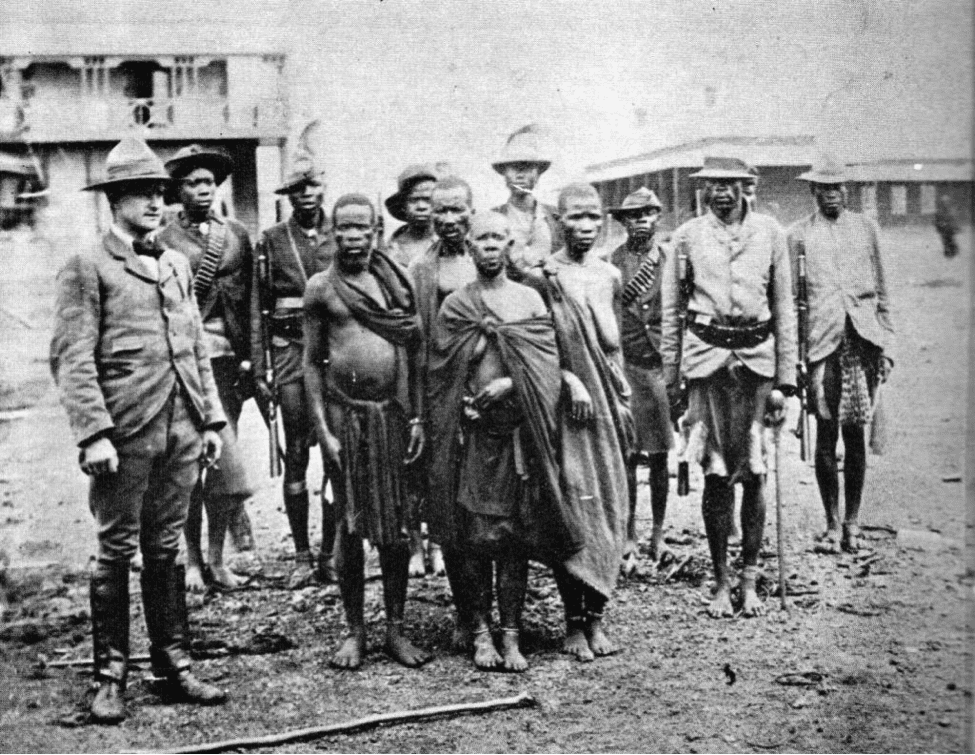 Image [Nehanda Mbuya (center) with soldiers and a British officer.]