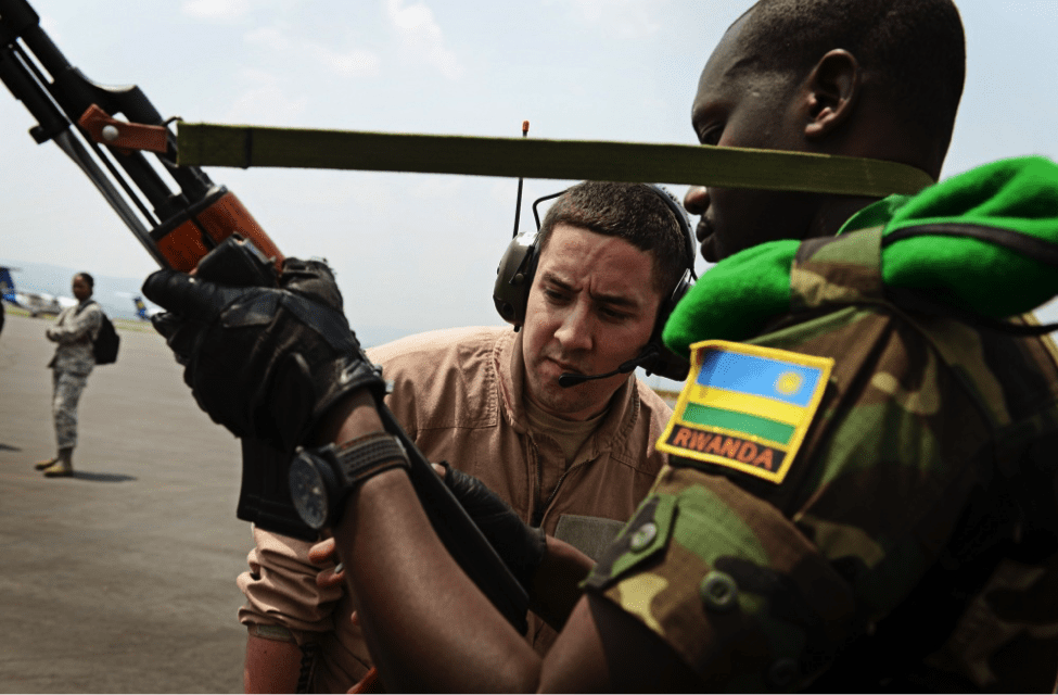 Image [U.S. soldier examines a weapon before allowing the soldier, and 850 other Rwandan soldiers, to board a U.S. Air Force plane in route to the Central African Republic to aid French and African Union operations. (U.S. Air Force photo/ Staff Sgt. Ryan Crane)]