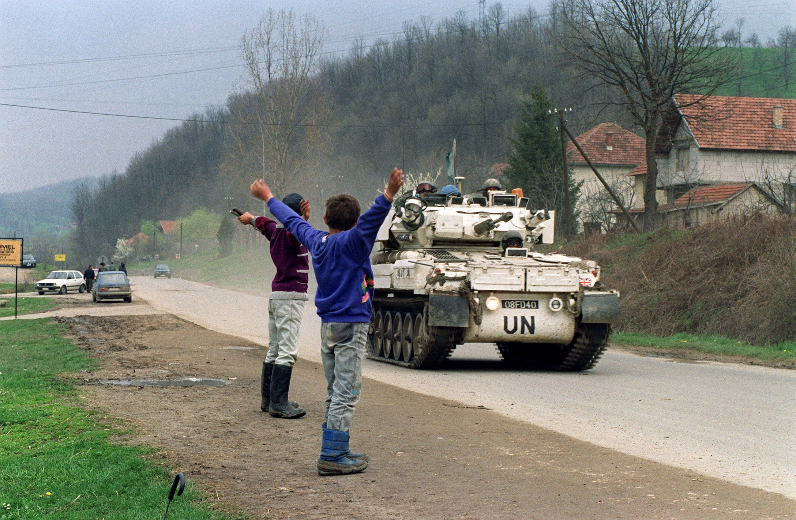 Image Two Bosnian boys salute a U.N. convoy departing for the Muslim enclave of Srebrenica, where some 30000 refugees awaited evacuation, April 17, 1993. (Pascal Guyout)