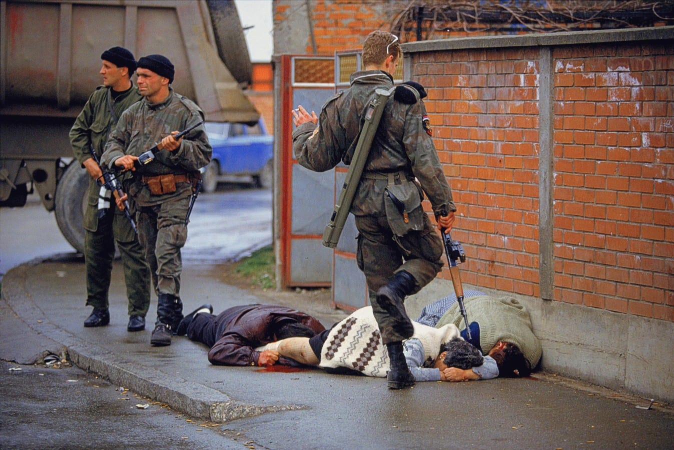 "Image [A member of the Serb nationalist militia known as the Tigers, led by Zeljko Raznatovic (""Arkan""), under the command of the Yugoslav People's Army (JNA) controlled by Serbian President Slobodan Milošević, kicks a Muslim woman (Ajsa Sabanovic, white sweater) who had been shot and killed by Serb forces during the Bijeljina massacre, April 1-2, 1992 (Photo: Ron Haviv)]"