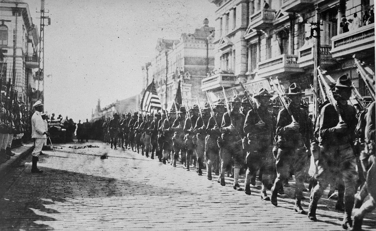 Image American troops in Vladivostok parading before the building occupied by the staff of the Czecho-Slovaks. Japanese marines are standing to attention as they march by. Siberia, August 1918. NARA.