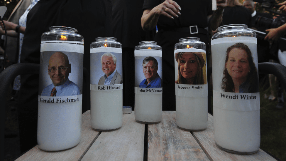 Image The photos of five murdered Capital Gazette employees adorn candles at a vigil in June in Maryland. (Jose Luis Magana)