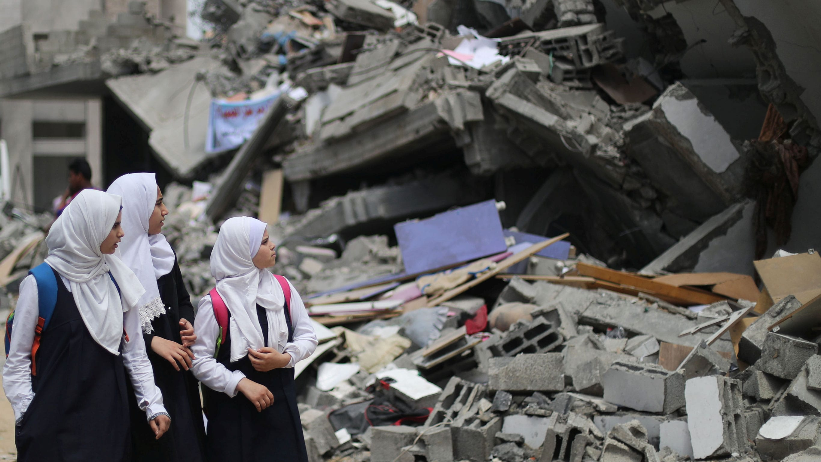 Palestinian students look at a building that was destroyed by Israeli airstrikes near their damaged school in Gaza City, Gaza, May 7, 2019. (Photo: Mohammed Salem / Reuters)]