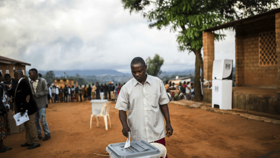 A man casts his vote, with long lines behind him, at Masasa Primary School polling station in Mzuzu on May 21, 2019. (Patrick Meinhardt)]